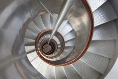 Metallic spiral stair with wooden handrails inside a lighthouse. Horizontal royalty free stock images