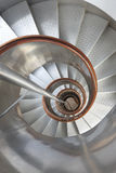 Metallic spiral stair with wooden handrails inside a lighthouse Stock Image