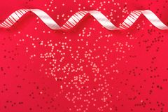 Metallic star shaped confetti on festive red background. stock image
