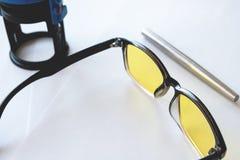 Metallic stylish fountain pen next to yellow glasses and print. White background Stock Photos