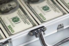 Metallic suitcase and dollar bills stock photos