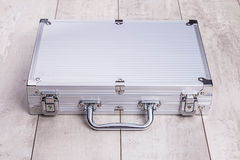 Metallic suitcase on wood background Stock Photo