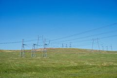 Overhead electricity transmission lines on a hill, in the summer. Metallic supports of overhead power lines on background blue skyin summer Royalty Free Stock Images