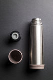 Metallic thermos over black background presentation Royalty Free Stock Photography