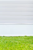 Metallic wall with green grass. Modern urban background Royalty Free Stock Image