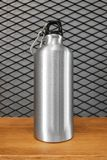 Metallic water bottle and carabiner on wood shelf background. Insulated container for your design. Metallic water bottle and carabiner on wood shelf background stock photo
