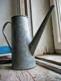 Metallic water jug. Jug on an old retro wooden window sill, vintage style background royalty free stock images