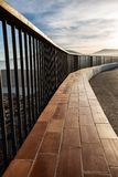 Metallic and wooden railing on a coast cliff illuminated by the sunset light stock photography