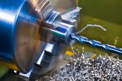 Drilling detail. Lathe working. Turning. Twisted metal swarf pile stock image
