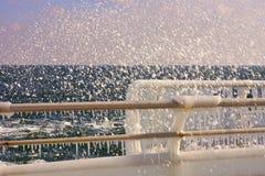 Metallico recinti il ghiaccio con la spruzzata della schiuma dell'onda Immagini Stock
