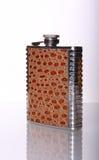 Metallische Flasche für alkoholisches Getränk auf Spiegeltabelle Lizenzfreies Stockfoto