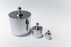 Metallische Gewichte auf weißem Hintergrund Stockfotos