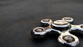 Metallische Seitenansichtnahaufnahme des Spinners auf dem Asphalthintergrund lizenzfreie stockfotos