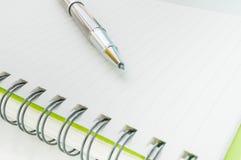 Metallischer Kugelschreiber auf Notizbuch Lizenzfreie Stockfotos