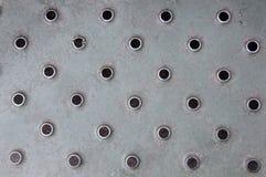 Metallischer Oberflächenhintergrund mit runden Perforierungen stockbilder