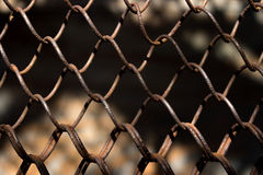 Metallischer rostiger Zaun in einem Gitterhintergrund Lizenzfreies Stockfoto