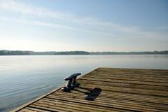 Metallischer Schiffspoller auf dem einsamen Pier am sonnigen Tag Lizenzfreies Stockbild