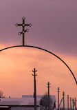 Metallisches christliches Kreuz und eine Reihe von elektrischen Pfosten Stockfotos