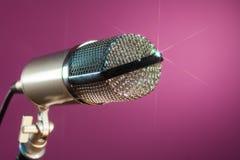 Metallisches Mikrofon auf rosafarbenem Hintergrund Stockbild