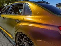 Metallisches orange Auto vom hinteren driver& x27; s-Seitenpassagier Lizenzfreie Stockfotos