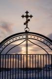 Metallisches Tor mit christlichem Kreuz, Sonnenunterganghimmel Lizenzfreie Stockfotografie