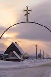 Metallisches Tor mit christlichem Kreuz, Sonnenunterganghimmel, kleines Dorfhaus Lizenzfreies Stockbild