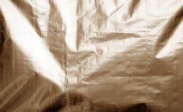 Metallisierte Plastikhüllebeschaffenheit mit zerknittert in der braunen Farbe stockfotografie
