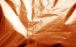 Metallisierte Plastikhüllebeschaffenheit mit zerknittert in der orange Farbe stockfotografie