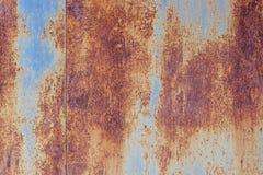 Metallisk blå bakgrund täckas nästan helt med rost, royaltyfri bild