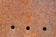 Metallisk brun bakgrund med tre hål Arkivfoto