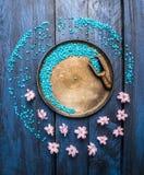 Metallisk bunke med det salta havet, skopan och blommor på den blåa trätabellen, wellnessbakgrund, bästa sikt Royaltyfria Bilder