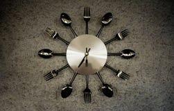 Metallisk gl?nsande klocka som g?ras speciellt f?r restauranggarnering med gafflar, skedar och knivar royaltyfri bild