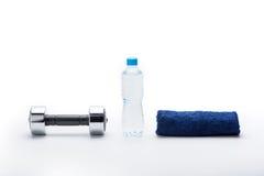 Metallisk hantel, handduk och flaska med vatten som isoleras på vit Royaltyfria Bilder