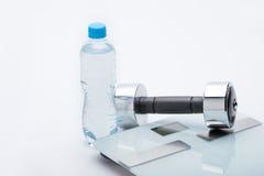 Metallisk hantel, våg, handduk och flaska med vatten som isoleras på vit Royaltyfri Foto