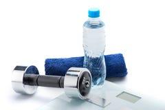 Metallisk hantel, våg, handduk och flaska med vatten som isoleras på vit Fotografering för Bildbyråer