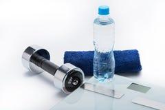 Metallisk hantel, våg, handduk och flaska med vatten som isoleras på vit Arkivbild