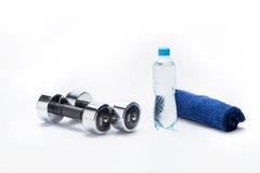 Metallisk hantlar, handduk och flaska med vatten som isoleras på vit Royaltyfri Foto