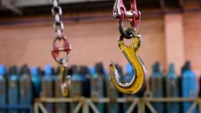 Metallisk industriell krok för att lyfta tung saker i fabriken Krankrokar på en tjock kedja inom fabriksgolvet stock video