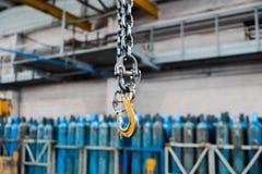 Metallisk industriell krok för att lyfta tungt ting i fabriken Krankrokar på en tjock kedja inom fabriksgolvet royaltyfria bilder