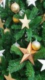 Metallisk julgran som dekorerar med den guld- stjärnasnöflingan och Arkivbilder