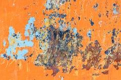 Metallisk orange bakgrund med skalningsmålarfärg- och blåttfläckar och arkivbild