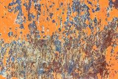 Metallisk orange bakgrund med skalningsmålarfärg och fläckar rostar, te arkivfoton