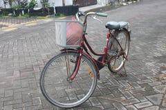 Metallisk röd stadscykel Arkivfoton