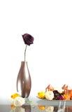 Metallisk vas med en rosblomma på tabellen över vit Modern garnering med vasen, blommar och stearinljus på en platta Arkivbilder