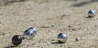 Metalliska bollar för petanque tre och en liten wood stålar Royaltyfri Bild