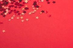 Metalliska konfettier på festlig röd pappers- bakgrund arkivbild
