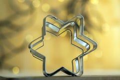 Metalliska stjärnaskärare för jul i magiska julljus på bakgrund Royaltyfri Fotografi