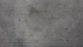Metalliskt grått fast galler för abstrakt bakgrund med små hål för en runda och asymmetriska svarta hål Fotografering för Bildbyråer