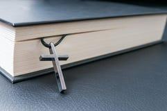 Metalliskt kors och helig bibel på svart bakgrund Fotografering för Bildbyråer