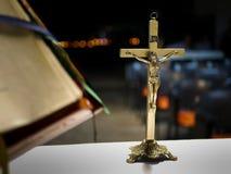 Metalliskt kors som förläggas på ett altare för en katolsk mass på natten med suddig bakgrund arkivbild